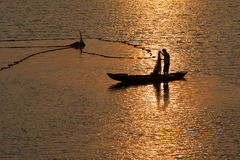 Fisher of man. A fisher is fishing in the lake at sunrise Royalty Free Stock Photography
