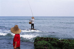 Fisher man and boy. Fisher Man and his son working in the Sea, in China Royalty Free Stock Photos
