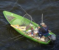 Fisher Man Fishing On Boat op Daugava-Rivier onder Brug in Riga stock foto's