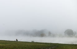 Fisher man fishing  on a river bank at misty foggy sunrise Stock Images