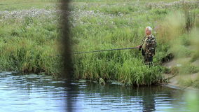 Fisher man med metspöet som fångar fisken på sjön arkivfilmer