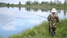 Fisher man med metspöet som fångar fisken på sjön lager videofilmer