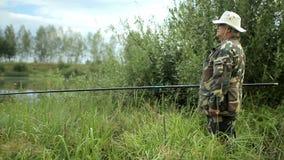 Fisher man med metspöet som fångar fisken på sjön stock video