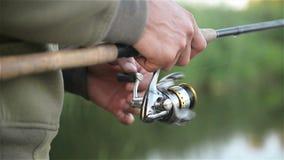 Fisher Man Mishing Over le lac au printemps Prises canne à pêche de pêcheur à la ligne La bobine est vue dans une fin  banque de vidéos