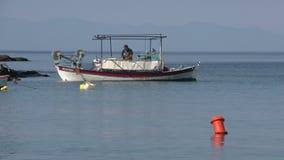 Fisher man som arbetar på hans fartyg på den Kemori stranden, Thassos, Grekland arkivfilmer