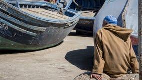 Fisher-Mann sitzt auf Hafenfront unter den blauen Instandsetzungs Booten stockfoto