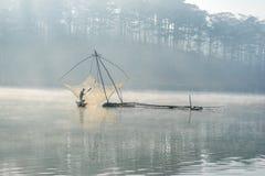 Fisher-Mannfische heraus auf dem See das Werkzeug des Fischermannes, sie unter Verwendung dieses für ihren Job, im nebeligen Stockfoto