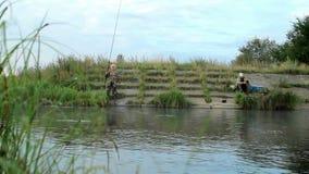 2 Fisher mans med metspöet som fångar fisken på sjön arkivfilmer