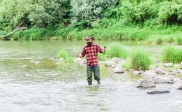 Fisher masculine hobby. Fish on hook. Brutal man stand in river water. Man bearded fisher. Fishing requires to be