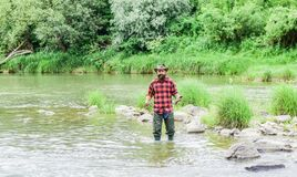 Fisher masculine hobby. Fish on hook. Brutal man wear rubber boots stand in river water. Satisfied fisher. Fishing