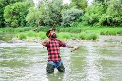 Fisher masculine hobby. Fisher fishing equipment. Fish on hook. Brutal man wear rubber boots stand in river water