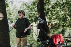 Fisher masculino positivo que guarda o equipamento de pesca profissional fotografia de stock