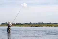 Fisher masculino que está em um rio com engrenagem de pesca com mosca Fotografia de Stock