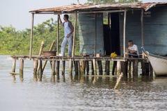Fisher mężczyzna siedzi w biednych drewnianych domach podnoszących up na Maracaibo Fotografia Stock
