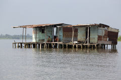 Fisher men sitting in poor wooden houses lifted up on Maracaibo. Fisher men sitting outside lifted up poor wooden houses standing on the lake Maracaibo and Royalty Free Stock Photography