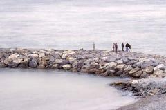 Fisher men on the stone groyne Royalty Free Stock Image