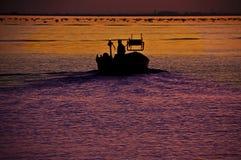 Fisher na motorowej łodzi przy pracą na morzu zmierzchem Fotografia Stock