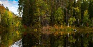 Fisher no barco está no lago da floresta no outono Imagens de Stock Royalty Free