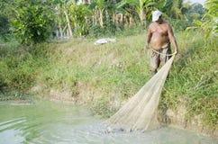 Fisher Old-Mann 60 Jährige unter Verwendung des Fischernetzfangwelses Lizenzfreies Stockfoto
