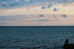 Fisher på pir på solnedgången Arkivfoton