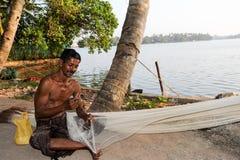 Fisher repairing his fishing net Royalty Free Stock Image