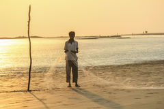 Fisher setting net on beach Royalty Free Stock Image