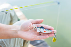 Fisher showing bait at fishing rod Royalty Free Stock Photography