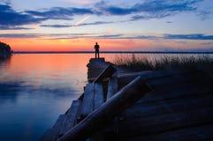 Fisher sull'uguagliare vecchio pilastro sul lago al tramonto immagini stock libere da diritti