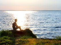 Fisher on a sunset. Fisher silhouette on sunset background stock photo