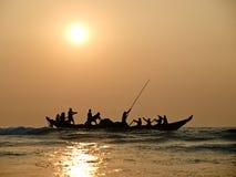 Fisher sur le bateau dans le coucher du soleil sur la mer Image stock