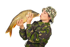 Fisher woman kissing the big fish. Fisher woman kissing big carp fish isolated on white background Royalty Free Stock Image