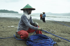 Fisher woman at work pulling the rope nets. Fishermen women a day just in salary of 2.5 dollars working time 07.00 am until 16:30 pm, to pull the fishing nets on stock image
