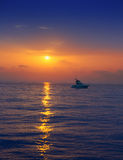 Fisherboat in horizon on sunset sunrise at sea. With sun reflection in blue water Stock Images