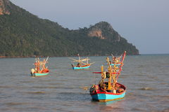 Fisherboats in the evening light. Three coloful fisherboats are floating in the sea, in Thailand near Prachuab. The boats are lit by the warm light of the Stock Images