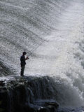 Fisherman. At a waterfall Stock Images