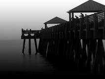 Fisherman. Low key image of people fishing on pier Stock Photography