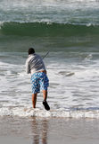 Fisherman. In the beach with waves Royalty Free Stock Photo