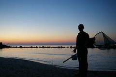 Fisherman. A fisherman with a net for crabs. Silhouette. The Baltic Sea Stock Photography