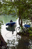 Fisherman. A fisherman in a boat on a lake and a bicycle royalty free stock photography