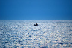 Fisherman. In a small boat on open sea stock image