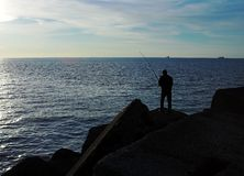 Fisherman. With rod on the mole Stock Photography