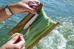 Fisherman. A fisherman preparing fishing hook in the sea Royalty Free Stock Photos