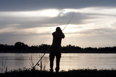 Fisherman. Silhouette of the fisherman on the river with a fishing tackle Stock Images