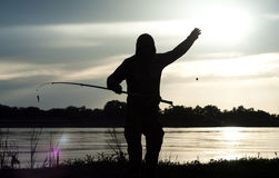 Fisherman. Silhouette of the fisherman on the river with a fishing tackle Royalty Free Stock Image