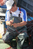 Fisherman. Mending his fishing net stock photos