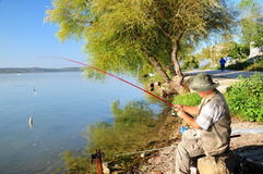 Fisherman. A fisherman is angling, sitting by lake stock images