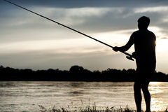 Fisherman. Silhouette of a fisherman with a fishing rod in the river at sunset Stock Photo