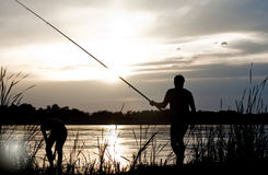 Fisherman. Silhouette of a fisherman with a fishing rod in the river at sunset Royalty Free Stock Photos