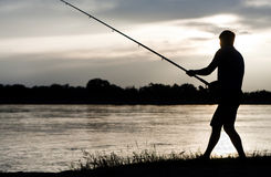 Fisherman. Silhouette of a fisherman with a fishing rod in the river at sunset Stock Photos