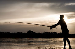 Fisherman. Silhouette of a fisherman with a fishing rod in the river at sunset Stock Photography